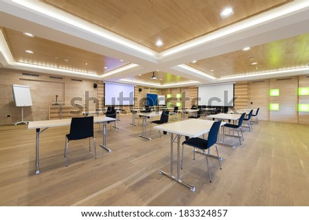 tables and chairs in modern wooden conference room with projection screens - stock photo