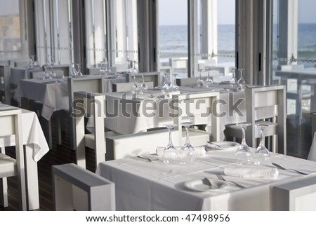 tables and chairs in stylish restaurant on an ocean coast, with sea view - Algarve, south of portugal - stock photo