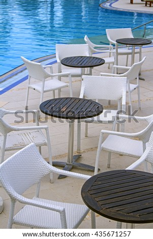 tables and chairs near the pool, table and chair near swimming pool in a tropical resort hotel, table and chairs near a cool pool in a hot canicular day - stock photo