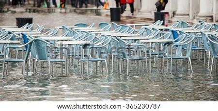 Tables and chairs with high water in Saint Mark's square, Venice, Italy. - stock photo