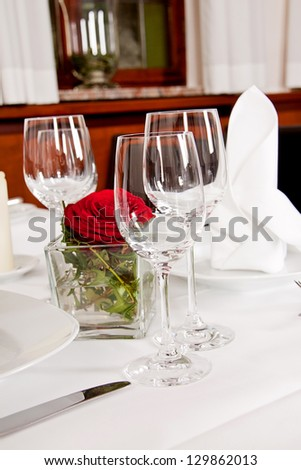 tables in restaurant with white tablecloth and elegant dish and silverwear - stock photo