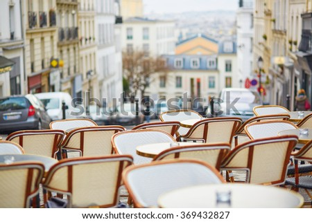 Tables of an empty Parisian outdoor cafe on Montmartre - stock photo