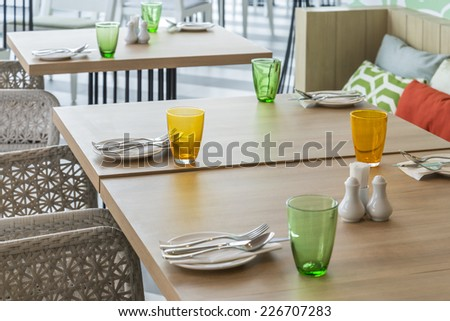 Tables set for meal in restaurant interior - stock photo