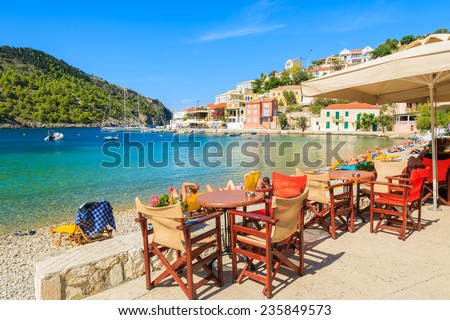 Tables with chairs in Greek tavern on beautiful beach in Assos village on Kefalonia island, Greece  - stock photo