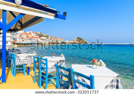 Tables with chairs in traditional Greek tavern in Kokkari town on coast of Samos island, Greece. - stock photo
