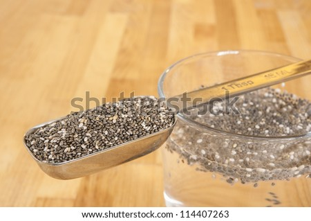 Tablespoon of chia seeds with chia seeds soaking in a glass of water - stock photo