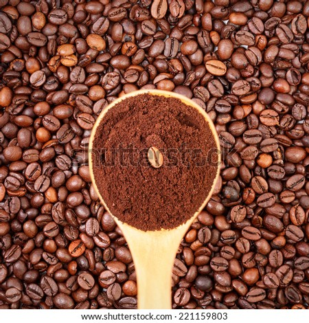 Tablespoon of ground coffee and coffee beans in the background - stock photo