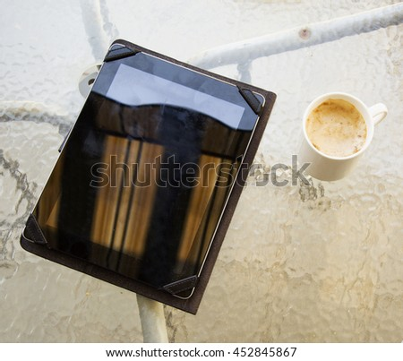 Tablet and cup of cappuccino, glass table, horizontal image - stock photo
