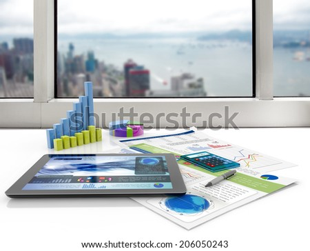 tablet and financial graphs on a white desk - stock photo