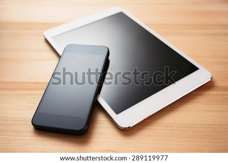 tablet and mobile phone on a wooden table - stock photo