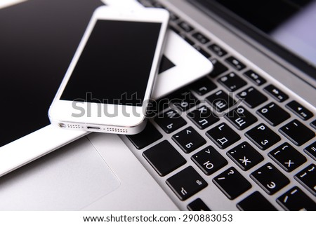 Tablet and mobile phone on keyboard, closeup - stock photo