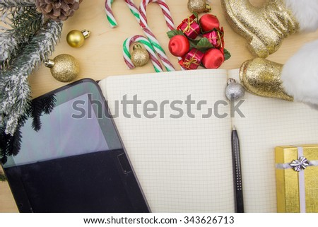 Tablet and open notebook with winter festive ornaments. - stock photo