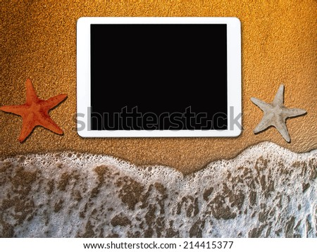 tablet at the beach - stock photo
