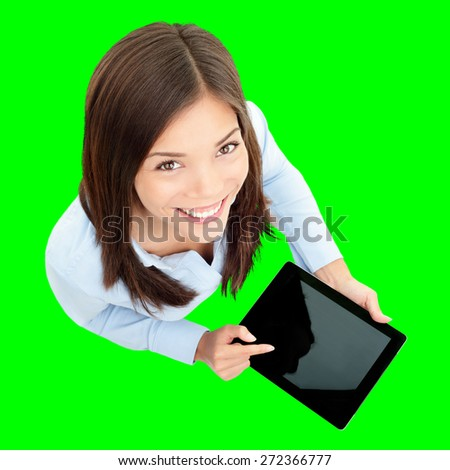 Tablet computer. Business woman using digital tablet computer PC happy isolated cutout on green background. Focus on both tablet and face. Woman in business shirt with finger on touch screen display. - stock photo