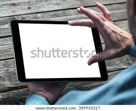 Tablet computer in male hands over table. Clipping path included. - stock photo