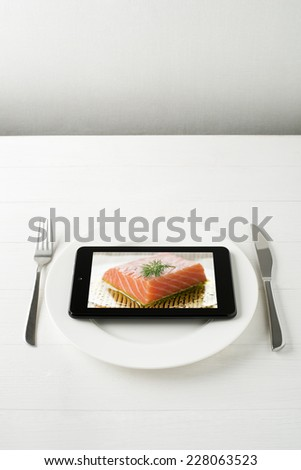 Tablet computer on a plate - mini photo on tablet is mine also. - stock photo