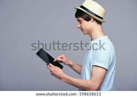 Tablet computer. Side view of man in blue tshirt and straw hat using digital tablet isolated on gray background. - stock photo