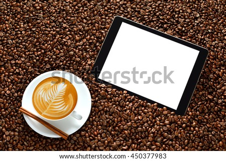 Tablet computer with blank white screen and cup of coffee latte on pile of coffee beans - stock photo