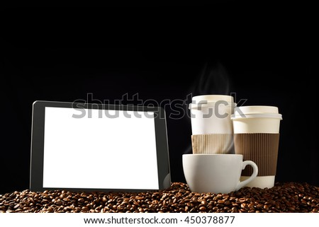 Tablet computer with blank white screen and cups of coffee with smoke on pile of coffee beans - stock photo