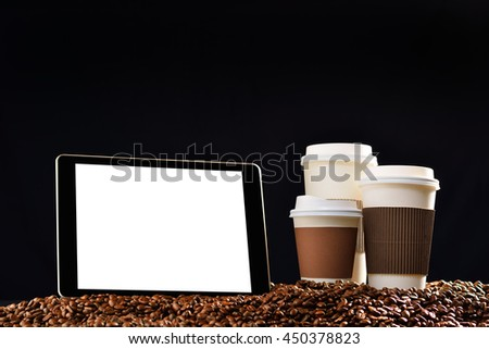 Tablet computer with blank white screen and paper cups of coffee on pile of coffee beans - stock photo