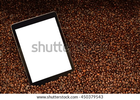 Tablet computer with blank white screen on pile of coffee beans - stock photo