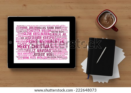 Tablet computer with christmas greetings tag cloud in a desk in many languages  - stock photo