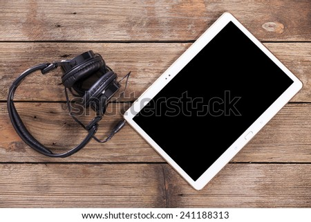 Tablet computer with headphones against wooden background - stock photo