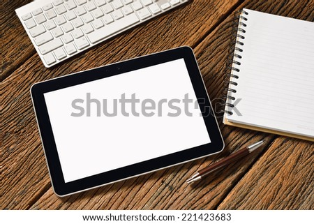 Tablet computer with notepad and keyboard on old wooden background - stock photo