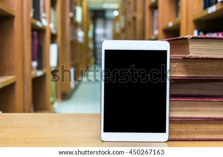 Tablet computer with old books on the wood table in library, Education concept - stock photo