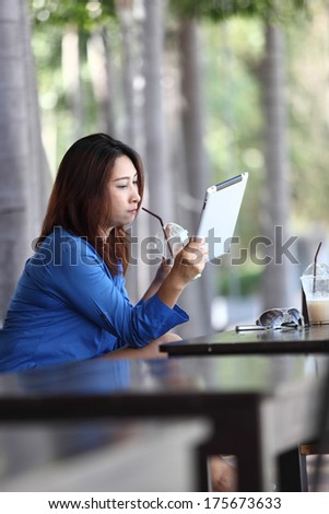 Tablet computer. Woman young smiling mixed race reading relaxed on  tablet  - stock photo