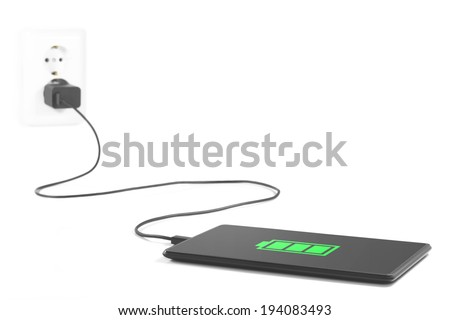 Tablet is charging from the power outlet on white background. - stock photo