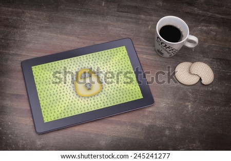Tablet on a desk, concept of data protection, yellow - stock photo