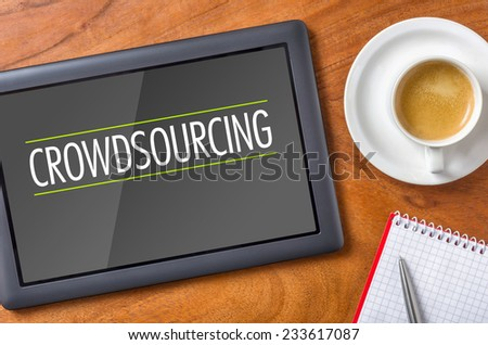 Tablet on a desk - Crowdsourcing - stock photo