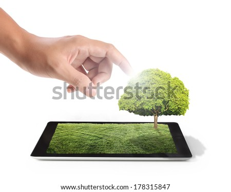 tablet on the white grass field and a tree - stock photo