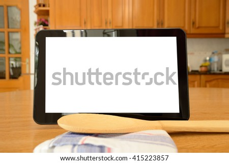 Tablet on wooden surface next a cloth and wooden kitchenware - stock photo