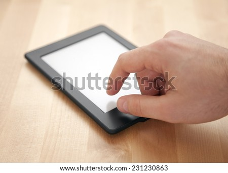 Tablet or e-book reader on wood background - stock photo