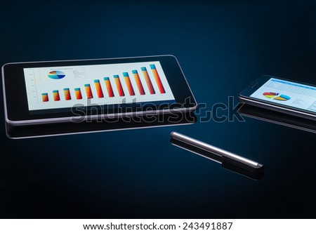 Tablet pc and smartphone with charts and report on screen - stock photo