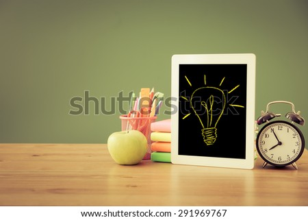 Tablet PC in classroom against green blackboard. Education concept - stock photo