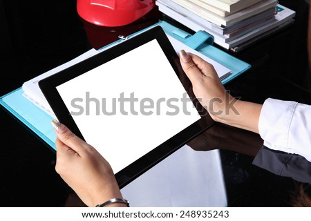 tablet pc in hand on office table - stock photo