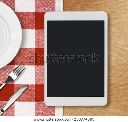 tablet pc looking lioke ipad on dinner table with fork and knife - stock photo