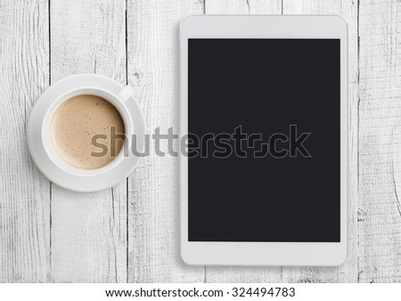 Tablet pc on white table desk with coffee cup - stock photo