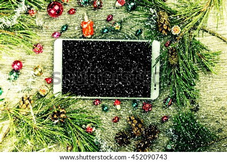 Tablet pc with blank screen and christmas fir tree with cones and christmas tree decoration on a wooden background. Template for banner or bavkground, or image for a blog. - stock photo
