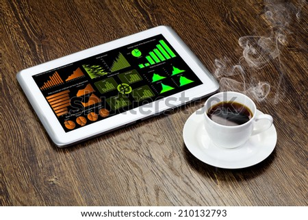 Tablet pc with graphs and cup of coffee on wooden table - stock photo