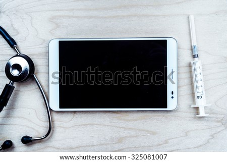 Tablet pc with medical objects on a desk as a metaphor for electronic diagnostic or healthcare mobile apps. Medical background - stock photo