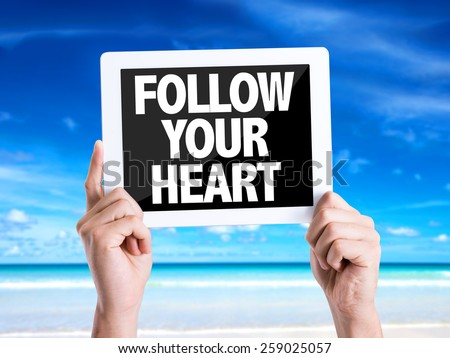 Tablet pc with text Follow Your Heart with beach background - stock photo