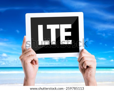 Tablet pc with text LTE with beach background - stock photo