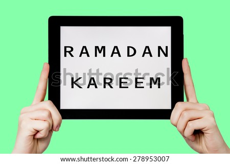 Tablet pc with text Ramadan kareem with green background - stock photo