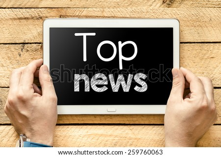 Tablet pc with top news. Male hands holding tablet pc with top news on wooden background - stock photo