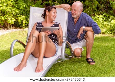 tablet reading seniors in garden explaining - stock photo