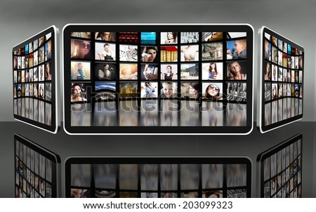 Tablet screens with many icons on dark background - stock photo